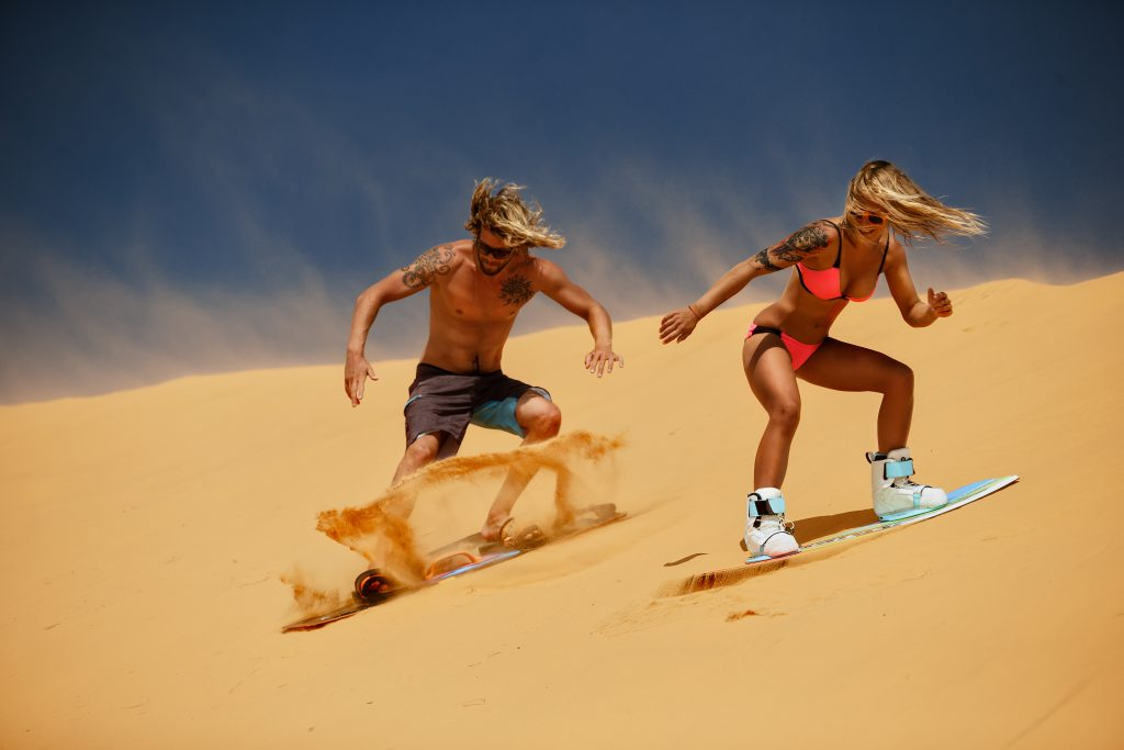 Woman and man sand surf